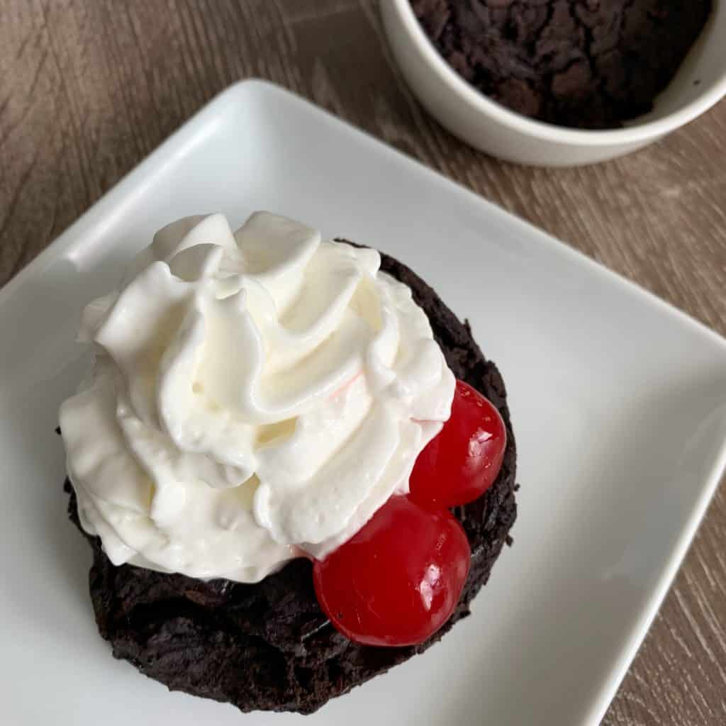 high protein cherry chocolate vegan mug brownie on a plate with whipped topping and maraschino cherries