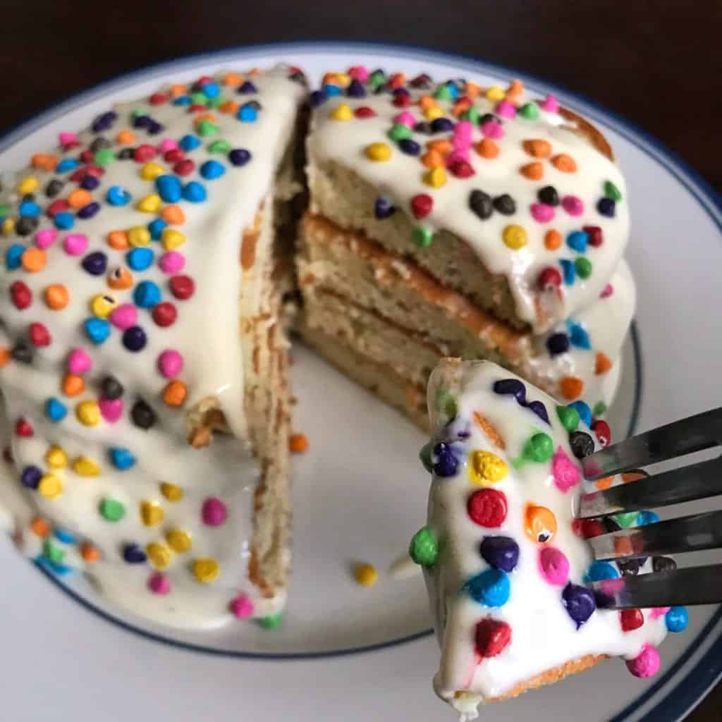 birthday cake protein pancakes on a plate with a section cut out for a bite