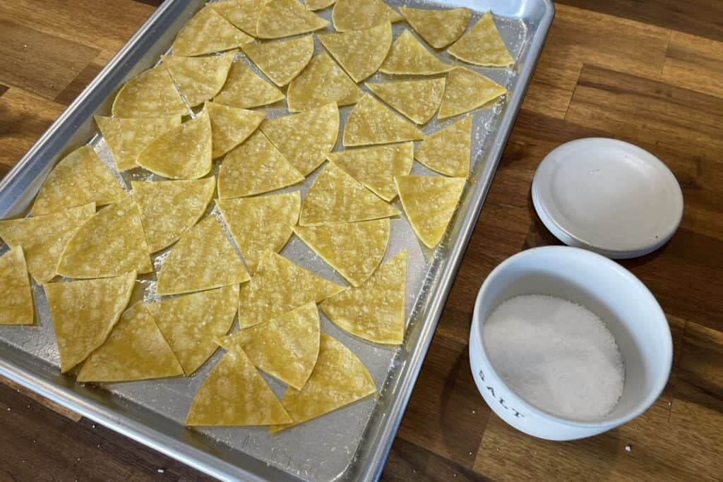 tortillas on a baking sheet with cooking spray and salt