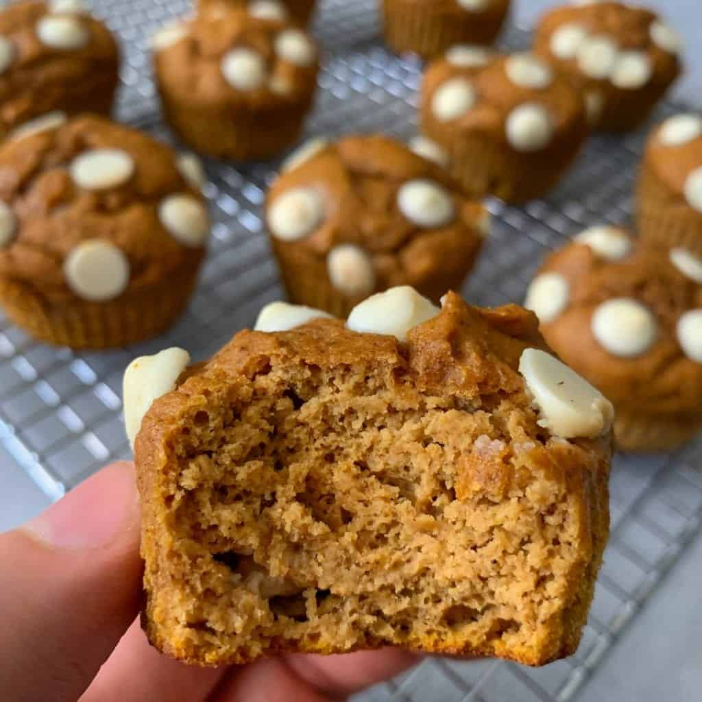 fingers holding a white chocolate pumpkin protein muffins