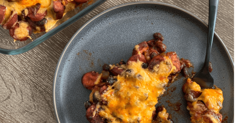 healthy chili dog tater tot casserole on a plate and the corner of the baking dish