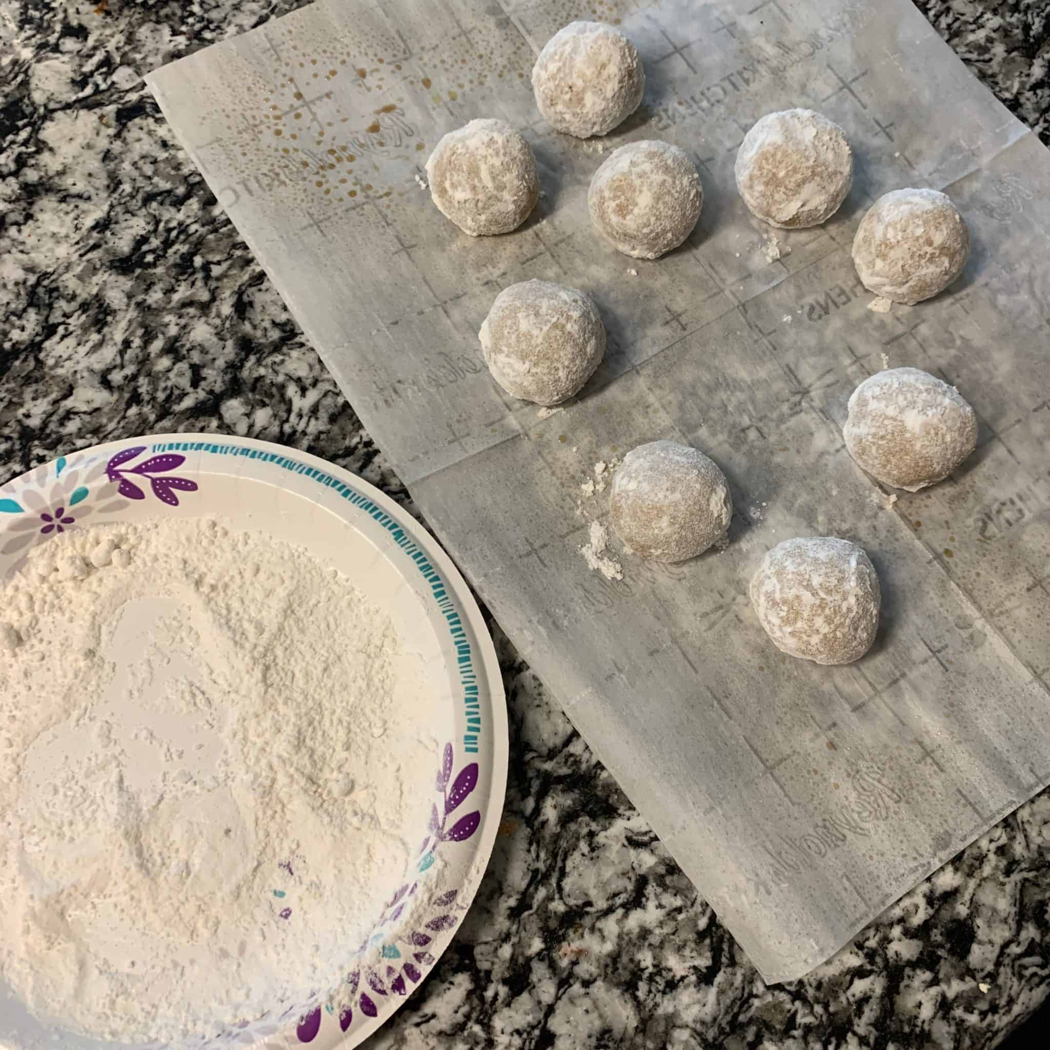 swerve confectioners on a plate with the gingerbread protein balls covered in powdered sugar