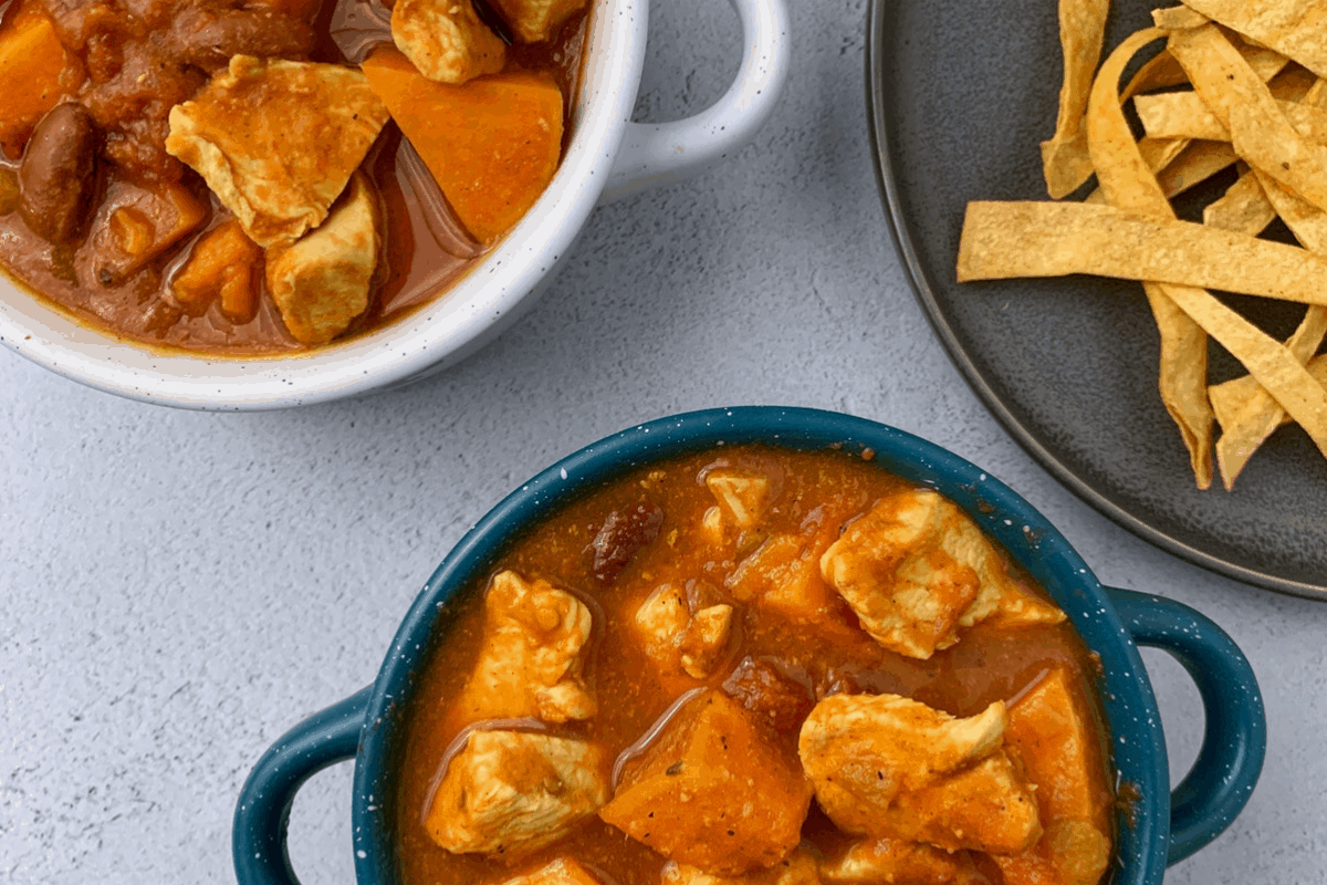 slow cooker sweet potato chipotle chicken chili recipe in two bowls with a plate of tortilla strips on the side