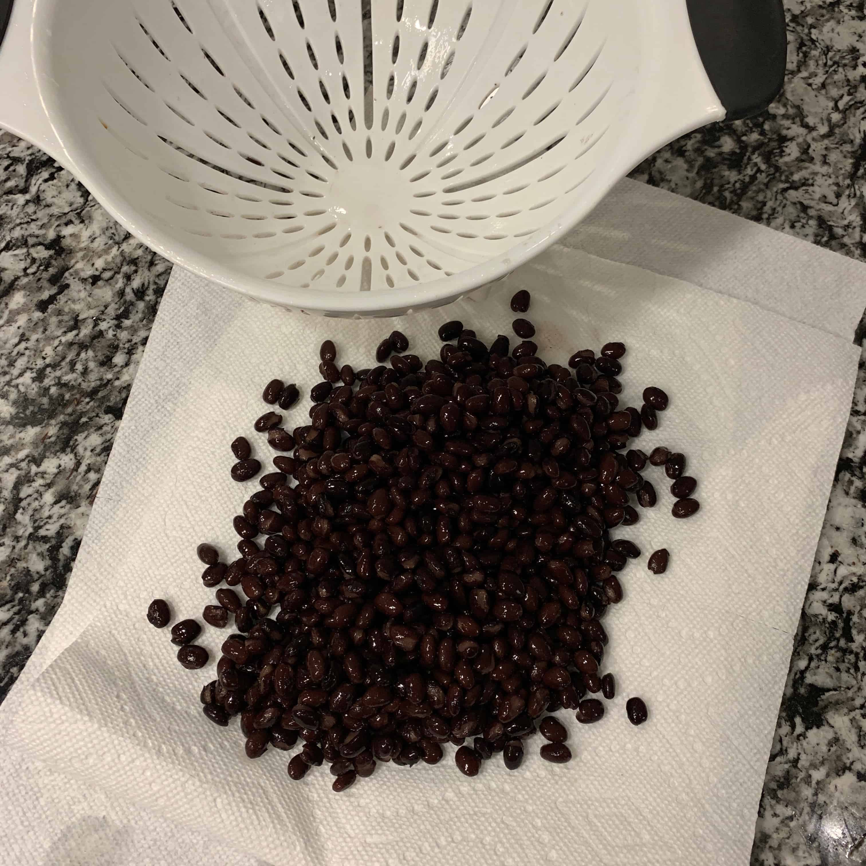 black beans by a colander on paper towels