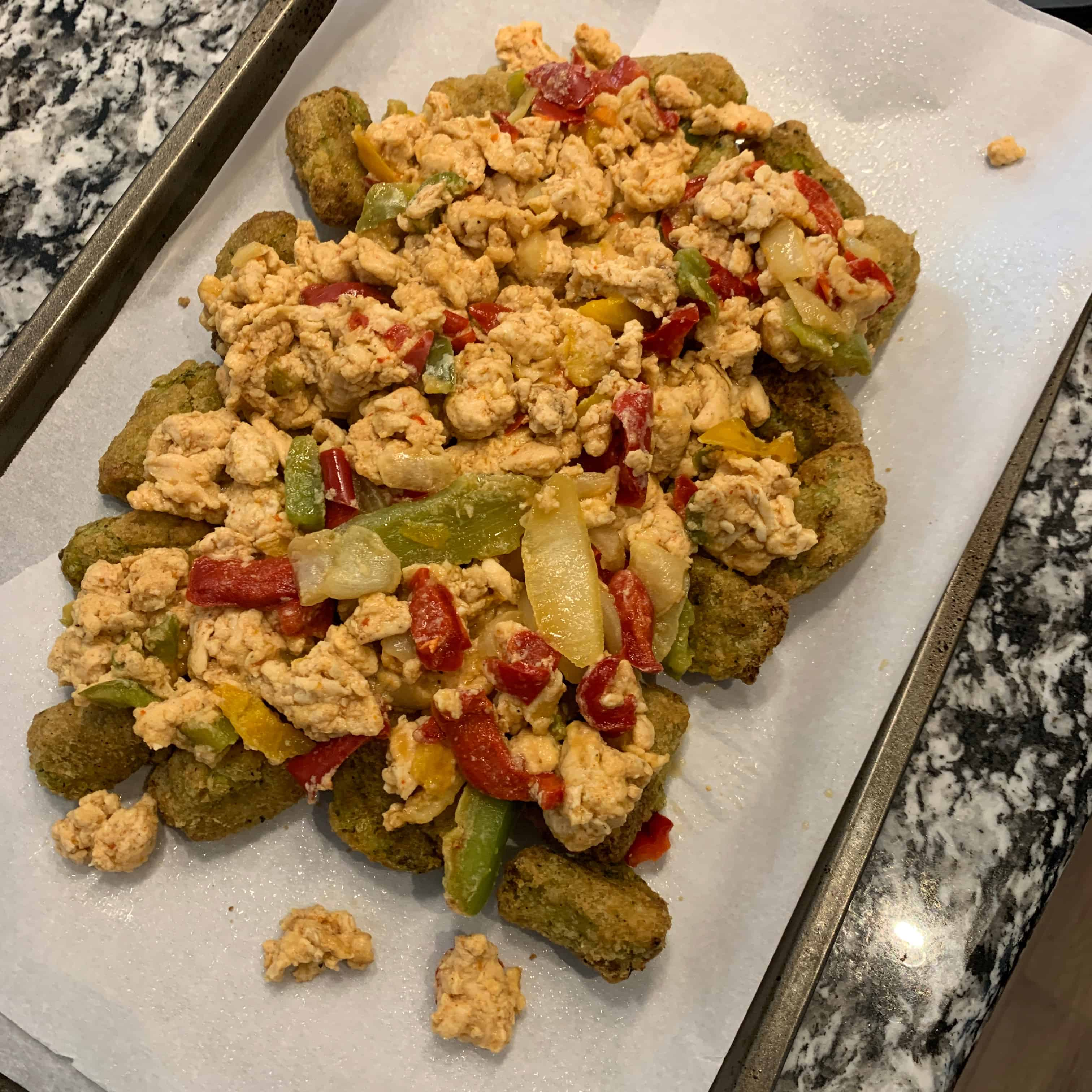 egg whites and peppers on top of cooked tots