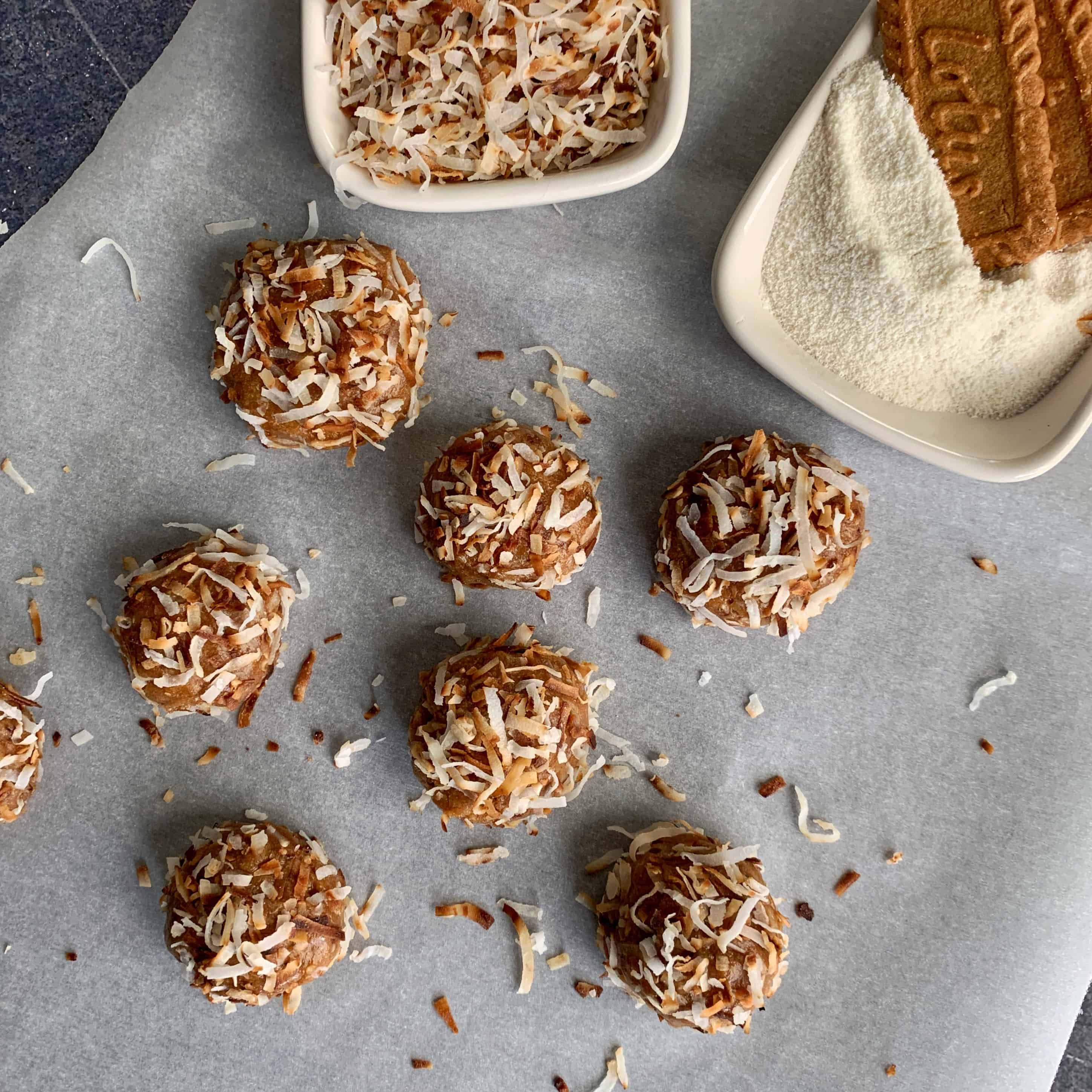 cookie butter protein balls beside a bowl of toasted coconut