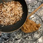 toasted coconut in a pan and the protein cookie butter in a bowl before combining the two