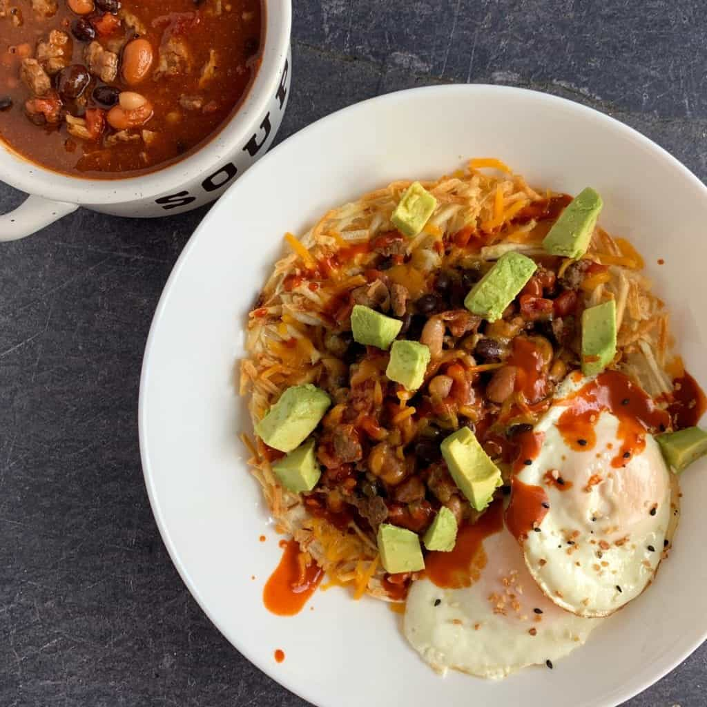 breakfast chili in a bowl and in a larger bowl over hash browns with cheese, avocado, and two fried eggs
