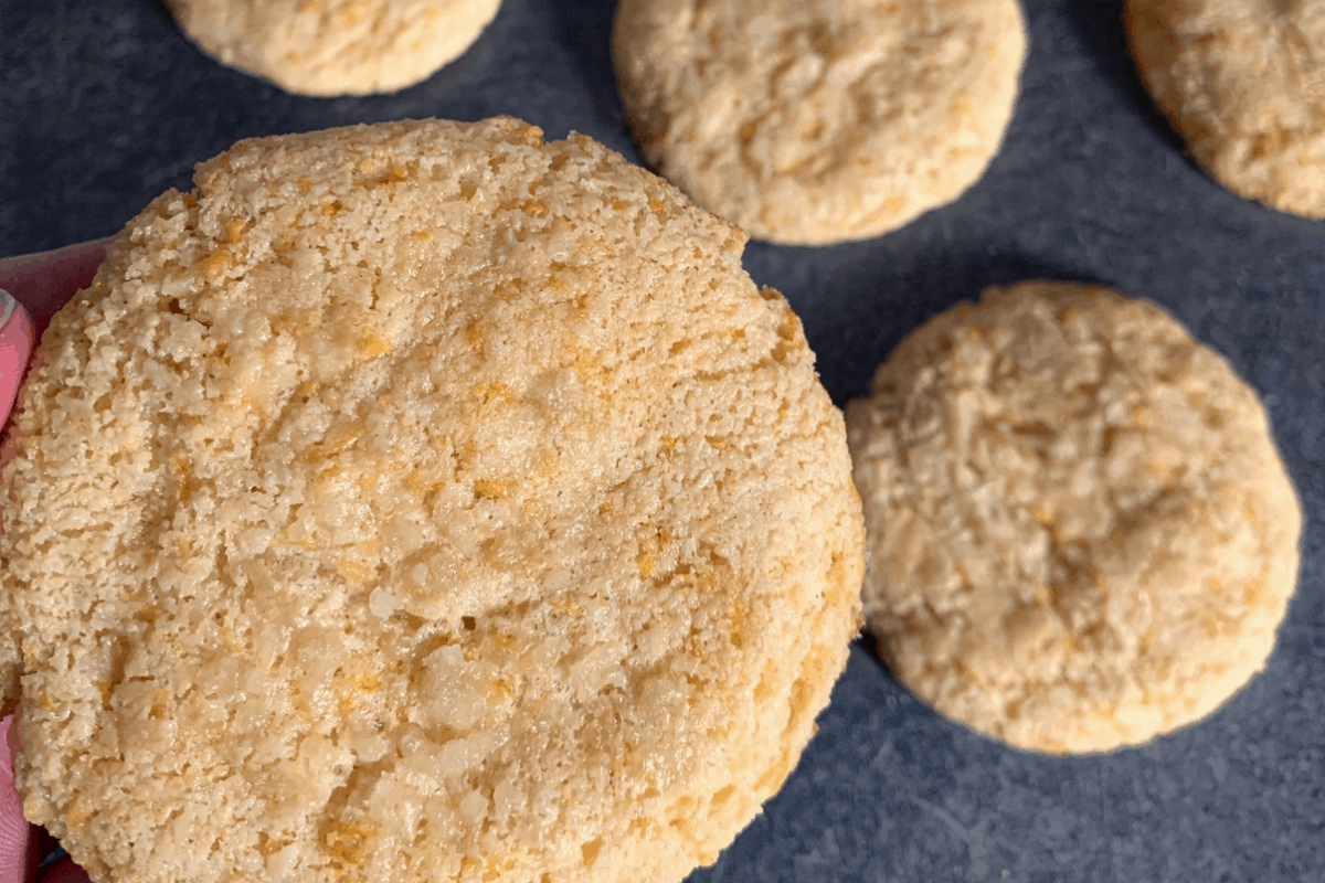 a lemon protein cookie being held above others on a dark surface
