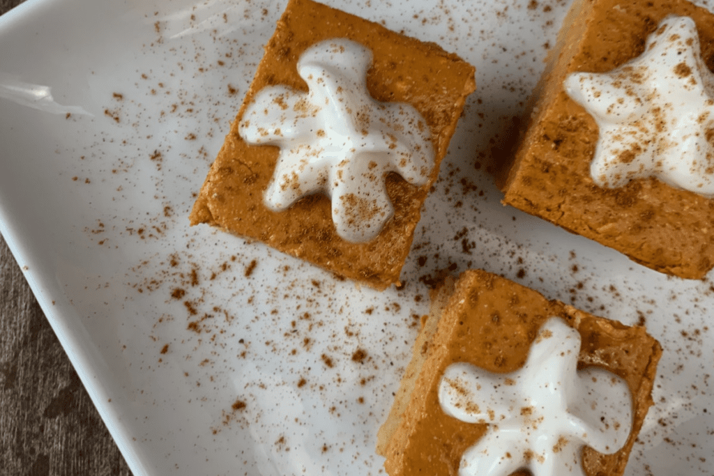 3 low carb pumpkin cheesecake bars on a white plate with ground cinnamon and whipped cream on top