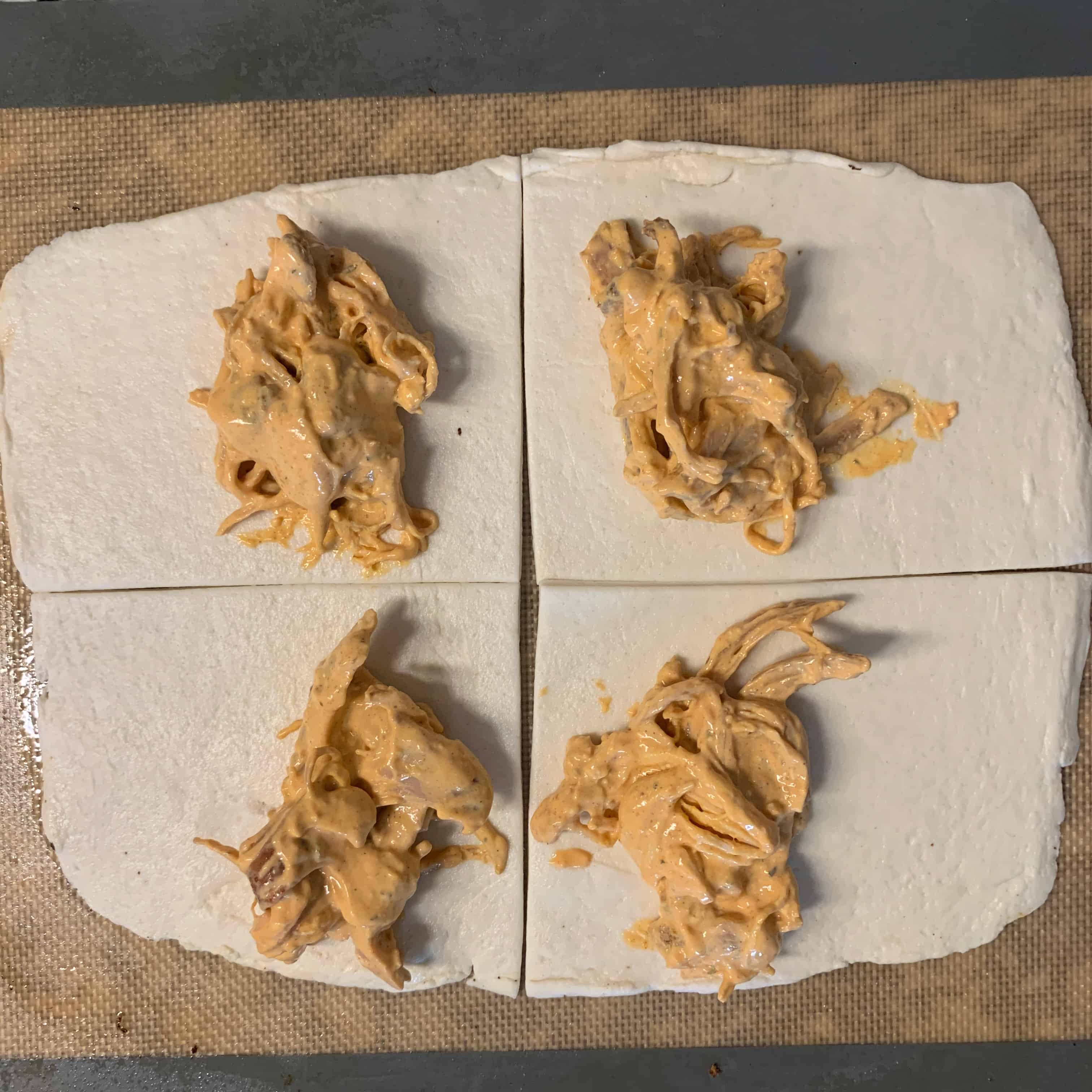 2 ingredient dough cut into 4 pieces with buffalo chicken on each piece