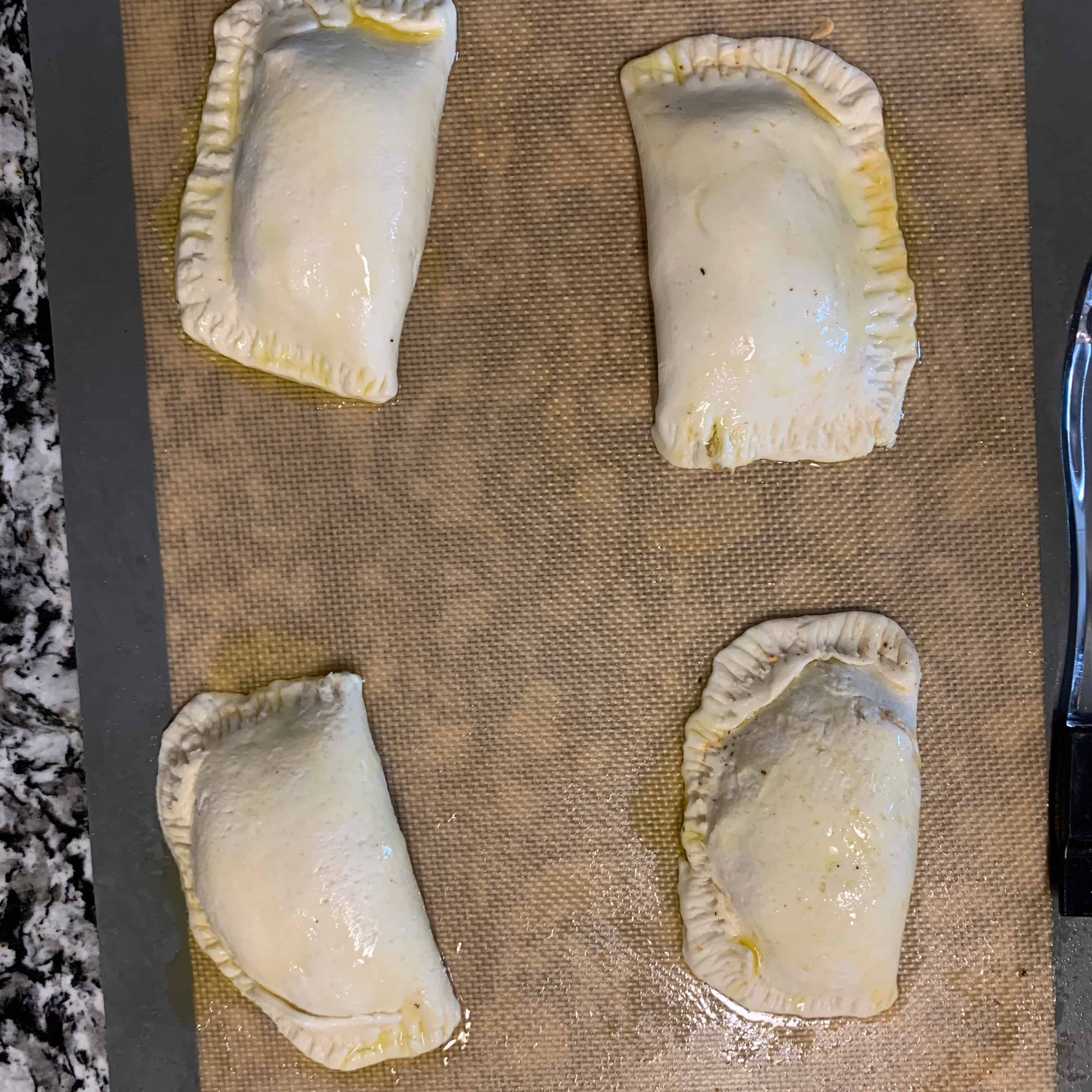 4 buffalo chicken empanadas with olive oil brushed on top and crimped edges before baking