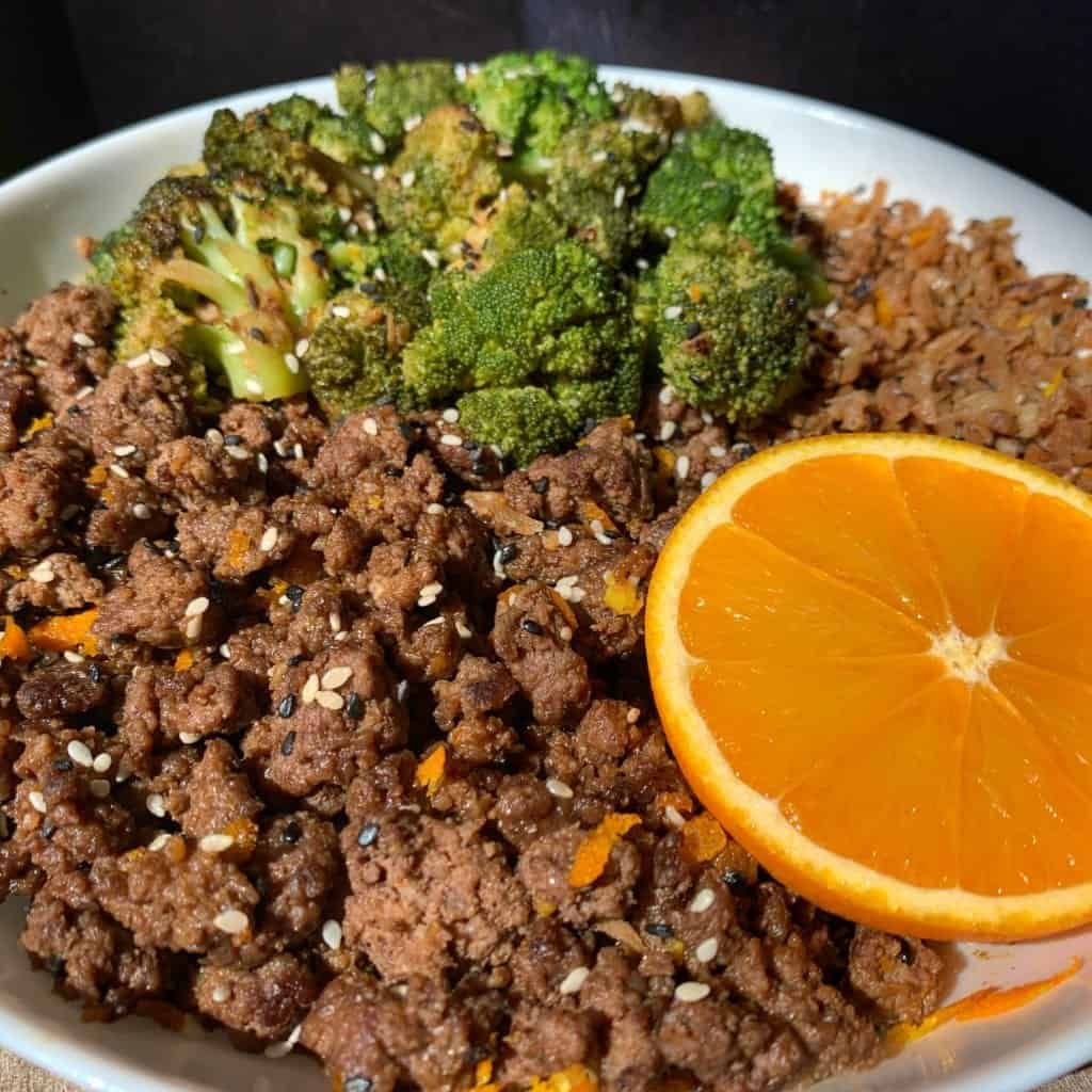 crispy orange beef in a white bowl with broccoli, fried cauliflower rice, and half an orange