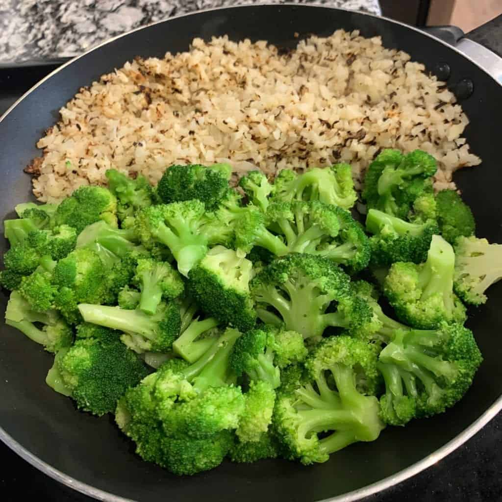 broccoli added to a skillet with fried cauliflower rice