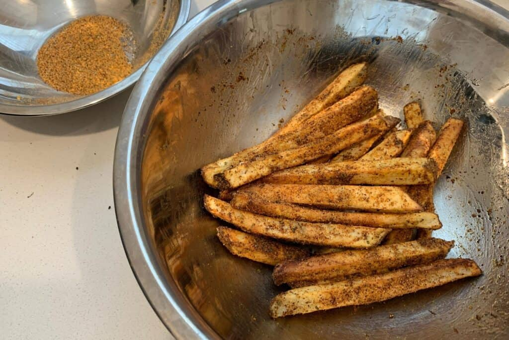 air fryer fries tossed in the nacho fries seasoning