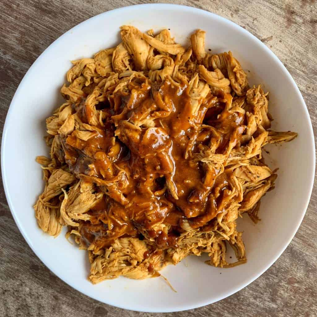 carolina bbq sauce over crockpot shredded chicken in a white bowl