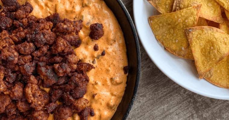 chorizo dip in a skillet with tortilla chips on a white plate