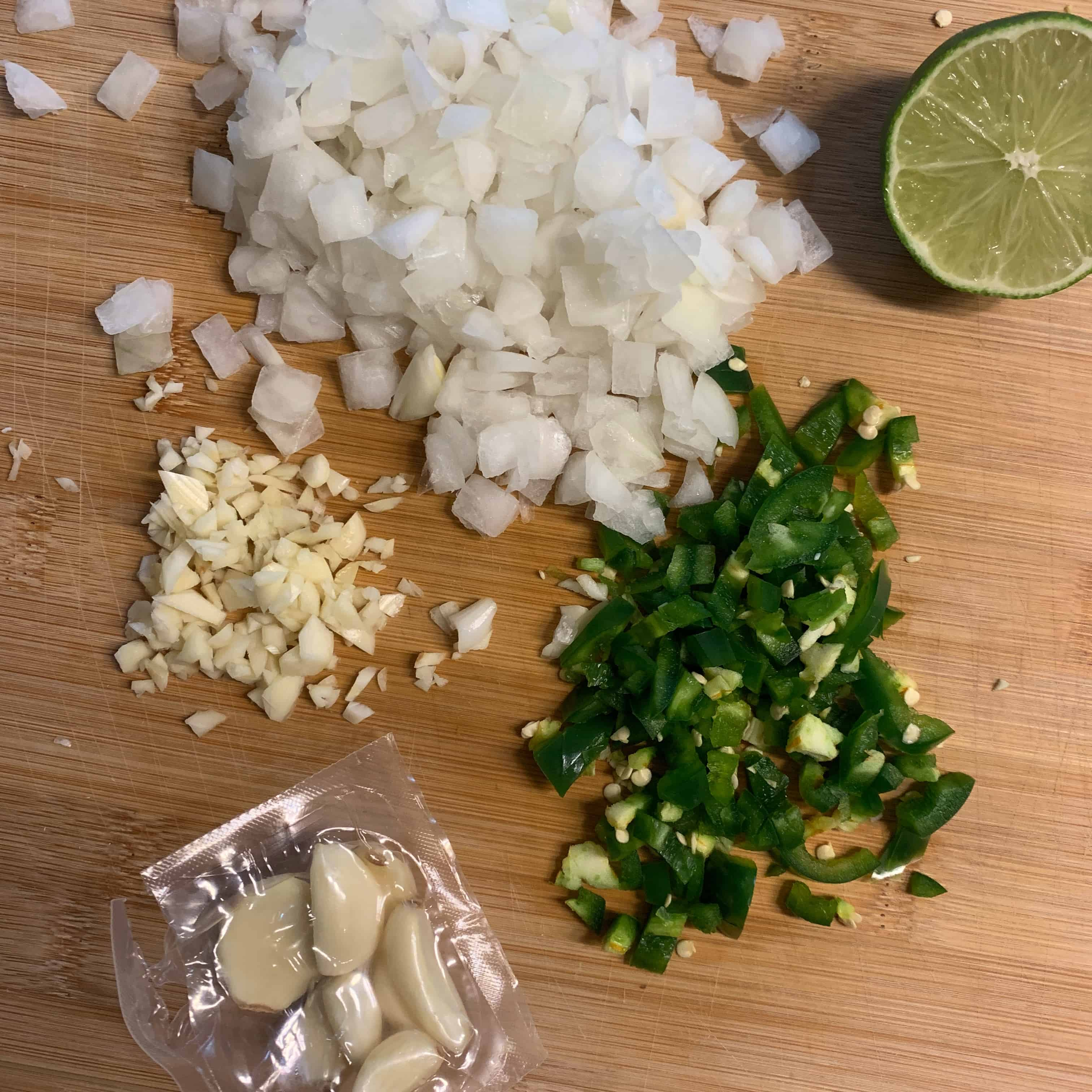 onion, jalapeño, and garlic on a cutting board with half a lime