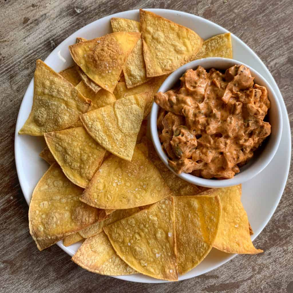 low calorie tortilla chips on a white plate with a bowl of chorizo dip