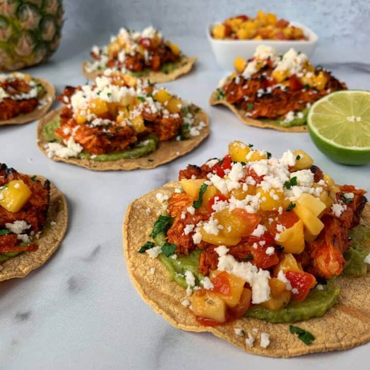 chicken tostadas on a white surface with a bowl of mango salsa