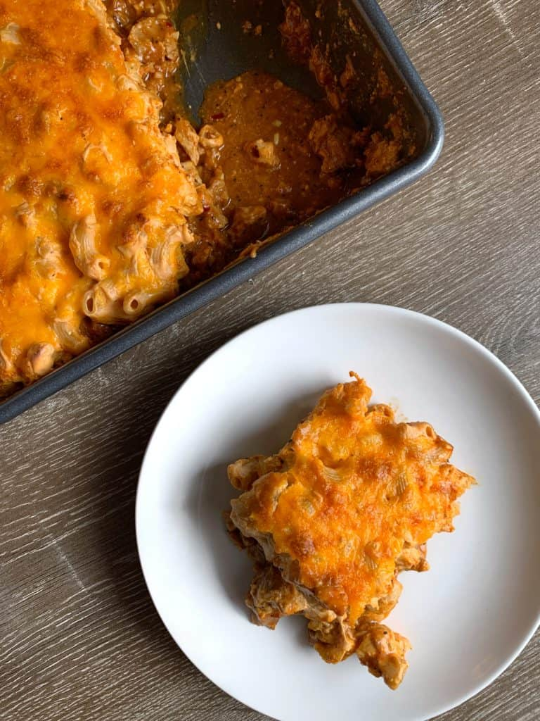 bbq pork mac and cheese bake on a plate beside the baking dish