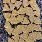 thin tortillas cut into triangles on a wire rack before baking