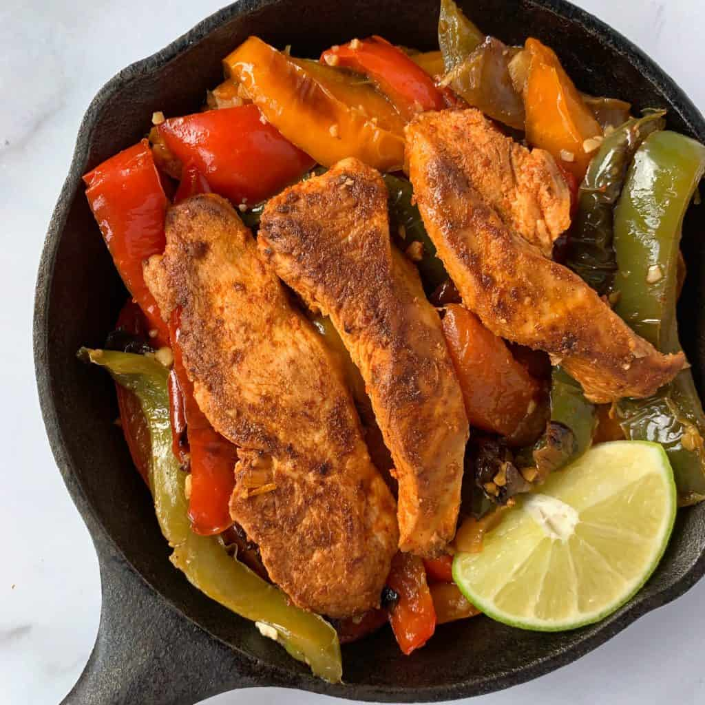 fajita chicken and peppers in a cast iron skillet