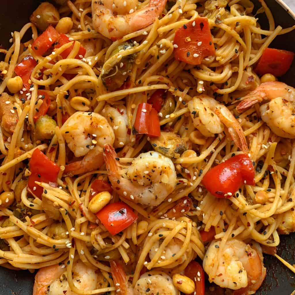 kung pao shrimp with red pepper and brussels sprouts on noodles
