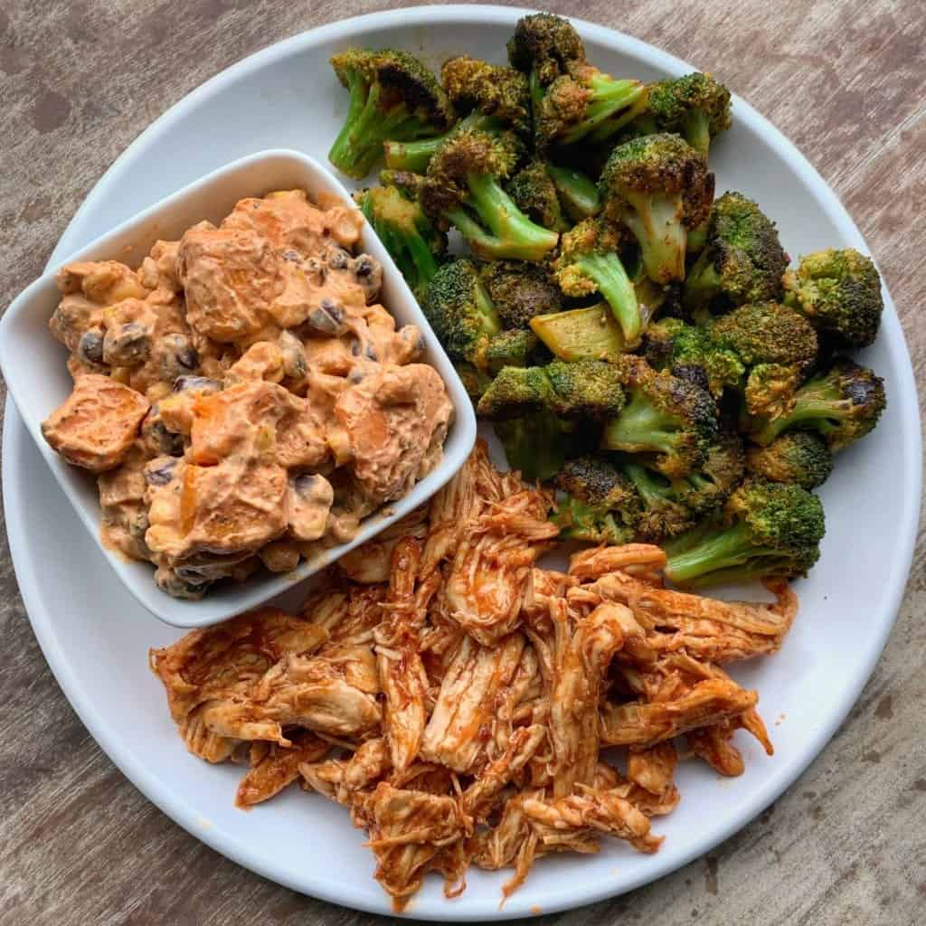 honey chipotle crockpot chicken on a plate with broccoli and sweet potato salad