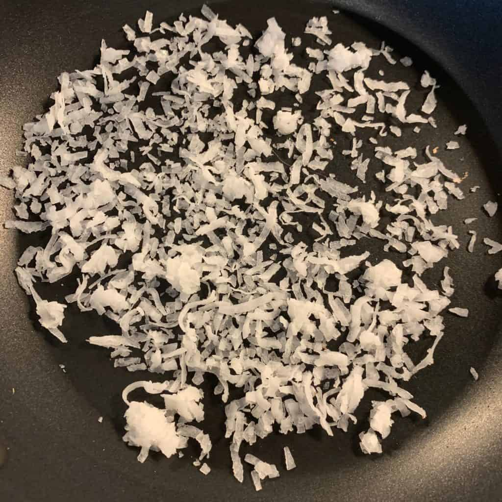 sweetened coconut flakes in a pan over medium heat