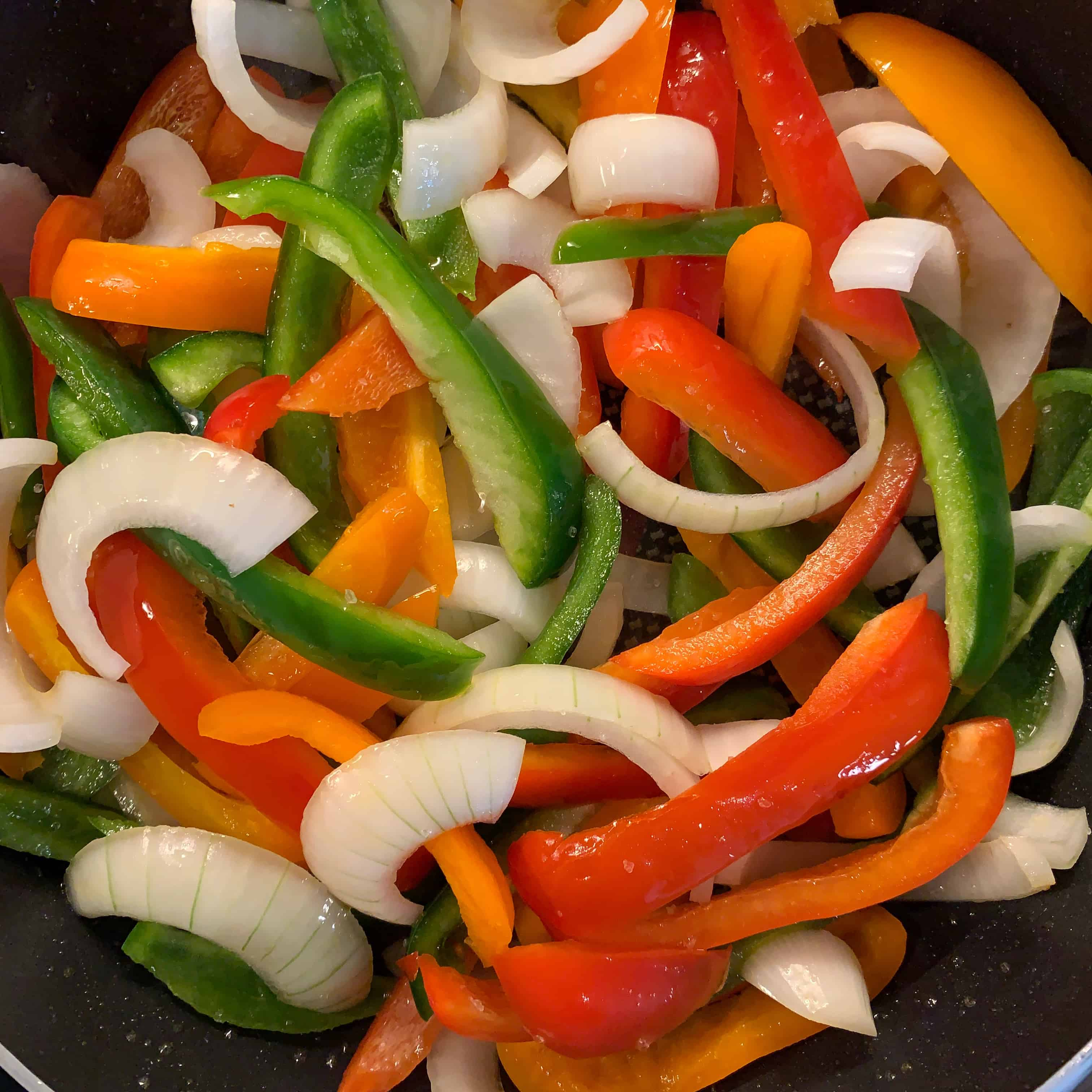 sliced peppers and onion in a skillet