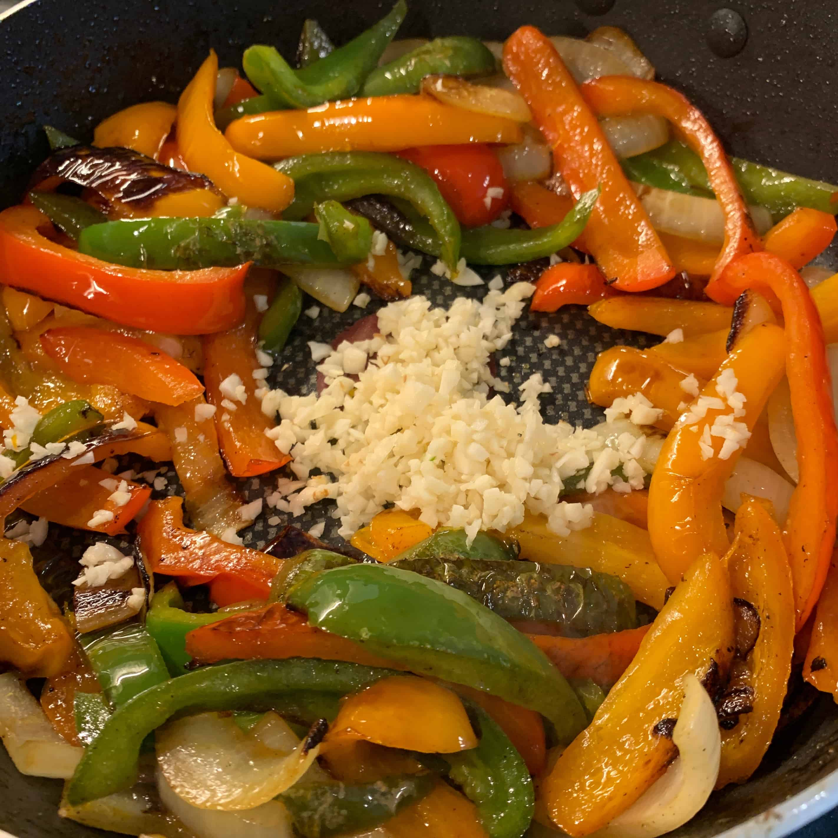 minced garlic in the skillet with sauteed peppers and onions