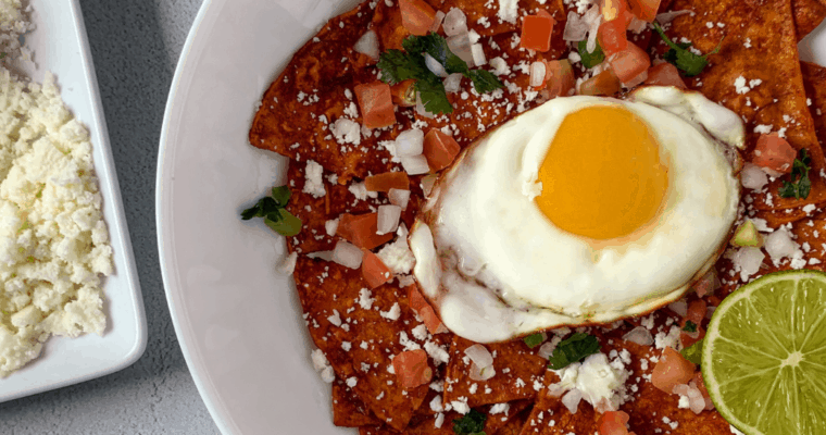 chilaquiles in a white bowl with crumbled cotija cheese beside it