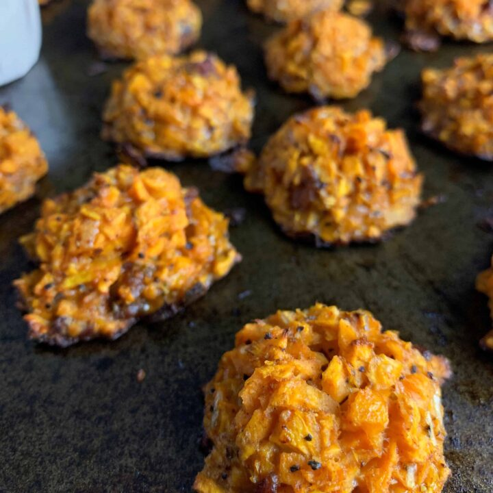 sweet potato tots on a baking sheet with a cup of honey dip in the background