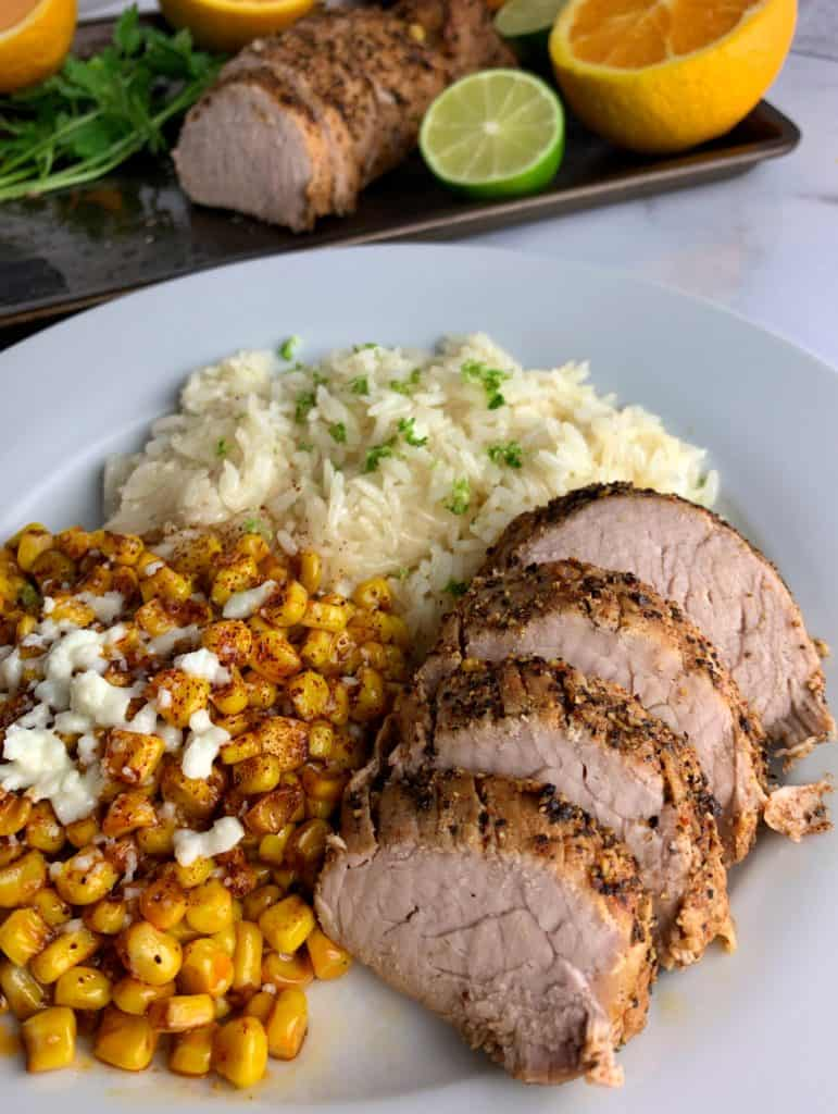 slices of the baked pork tenderloin with a side of corn and rice