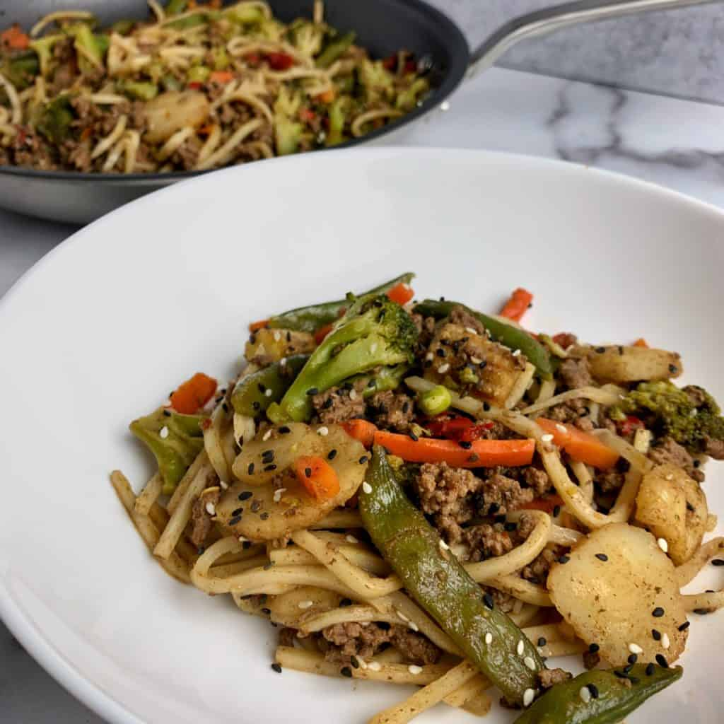 ground beef stir fry with noodles topped with sesame seeds