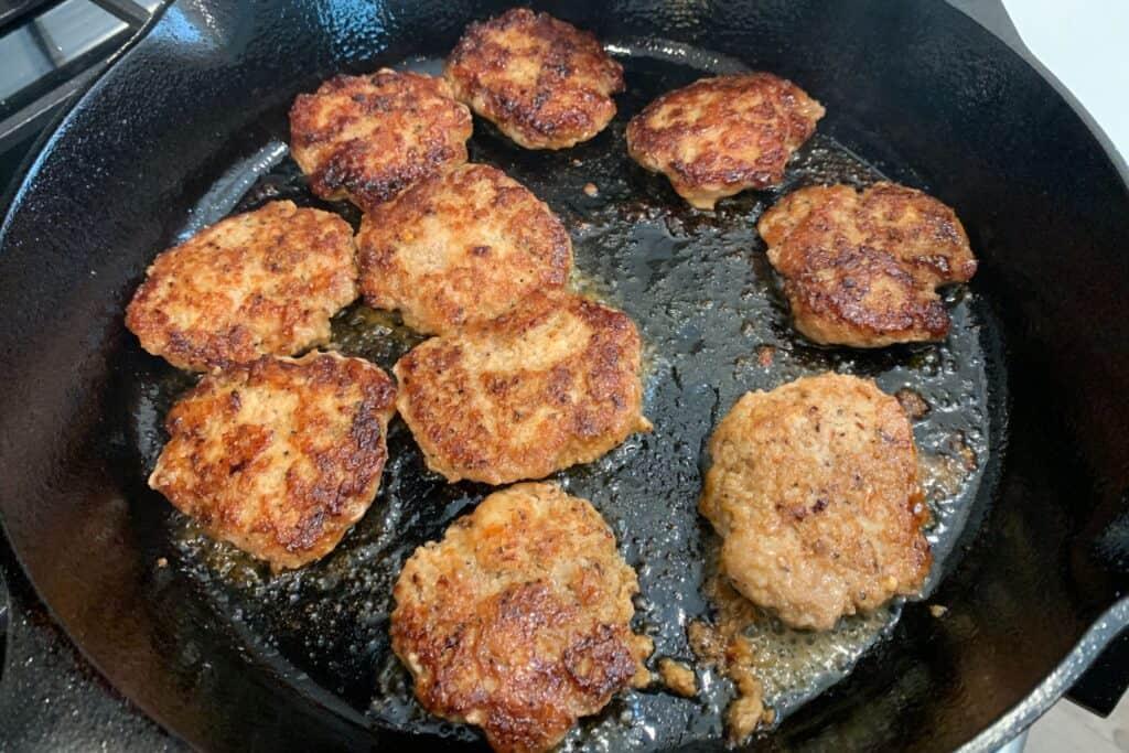ground chicken sausage patties after flipping halfway through cooking