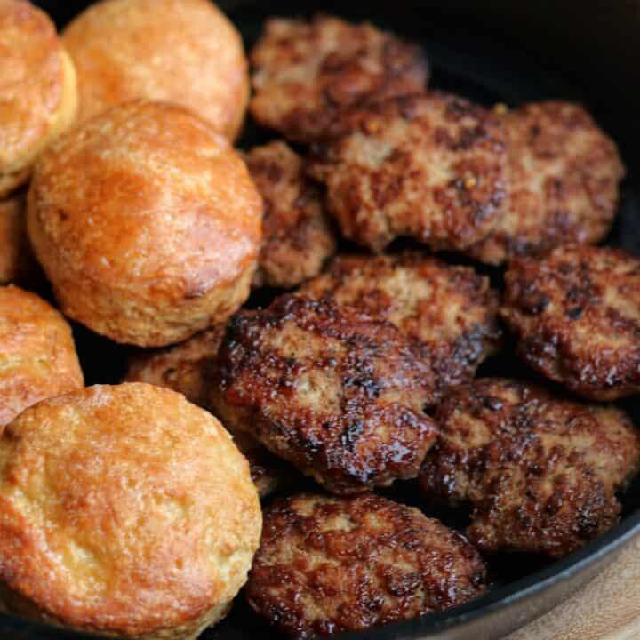 chicken breakfast sausage patties in a skillet with Greek yogurt biscuits