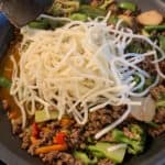 the vegetables and noodles on top of the cooked ground beef and five spice sauce