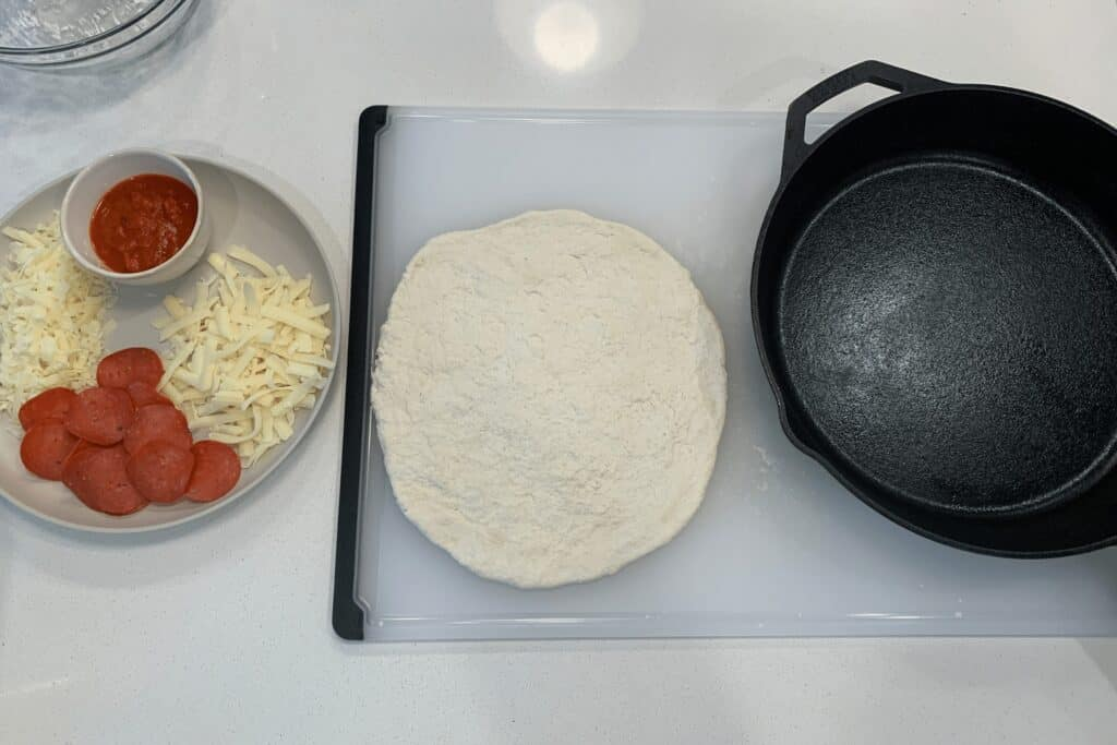 "Greek yogurt pizza dough next to a 12"" cast iron skillet and toppings"