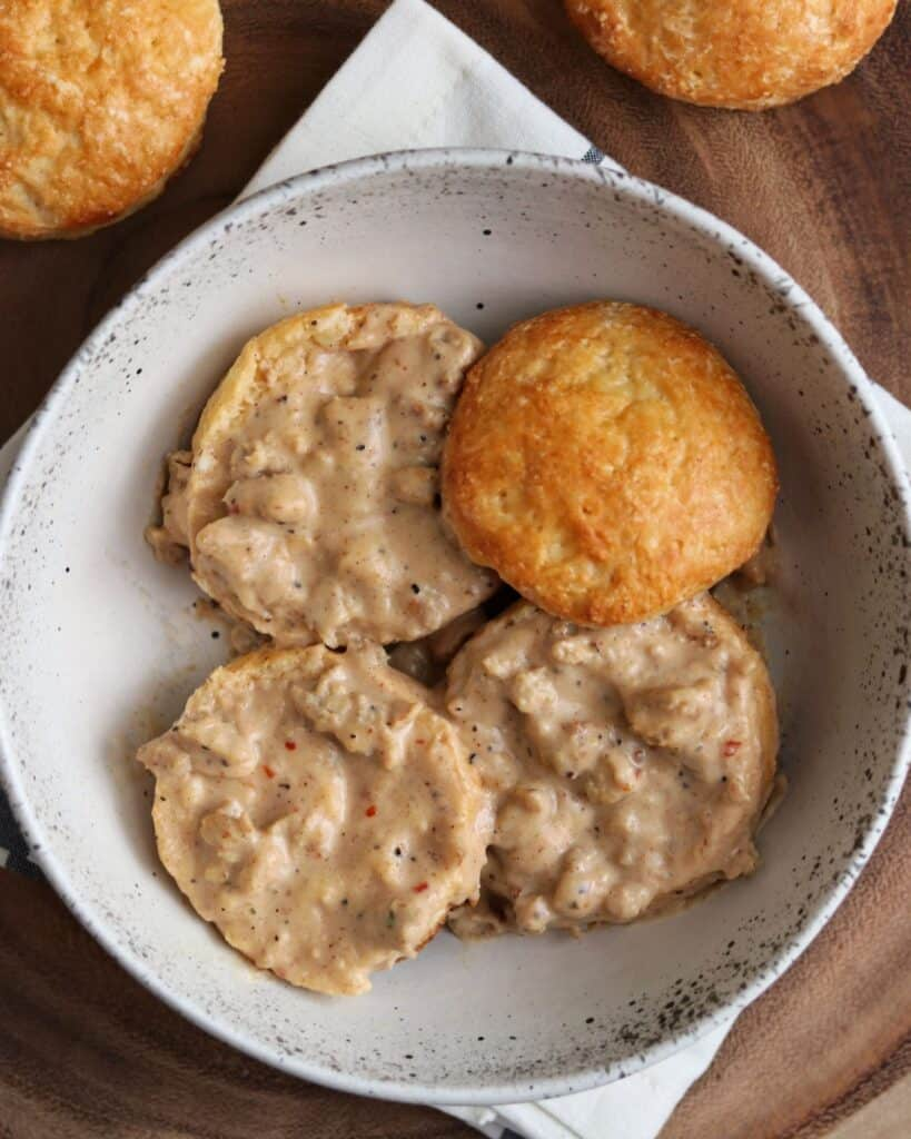 biscuits cut in half in a bowl with healthy sausage gravy