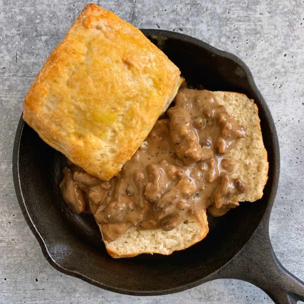 greek yogurt biscuits in a cast iron skillet with healthy sausage gravy over one