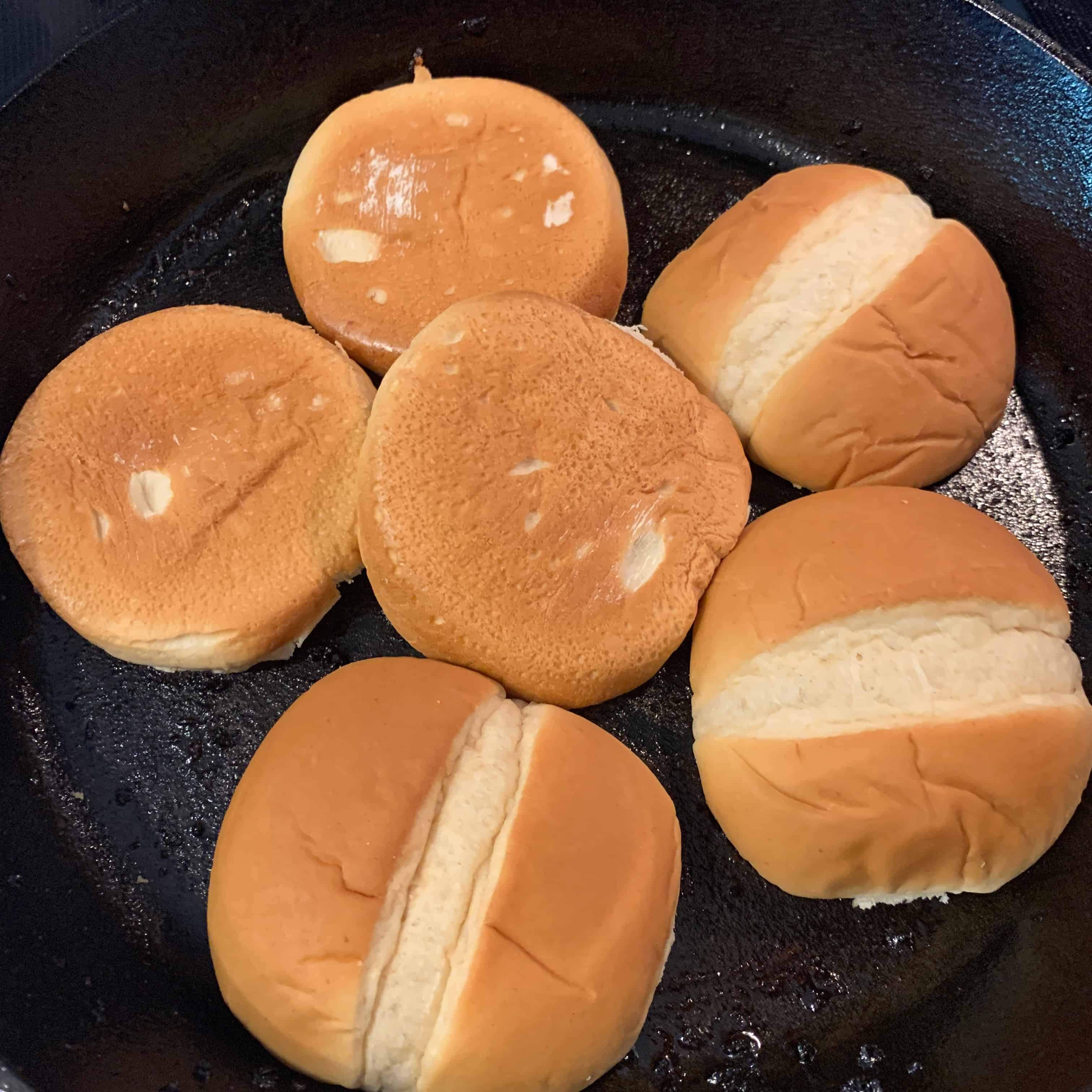 buns toasting in the skillet after cooking the chicken burgers