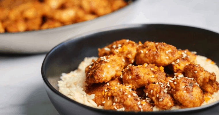 healthy baked orange chicken in a black bowl