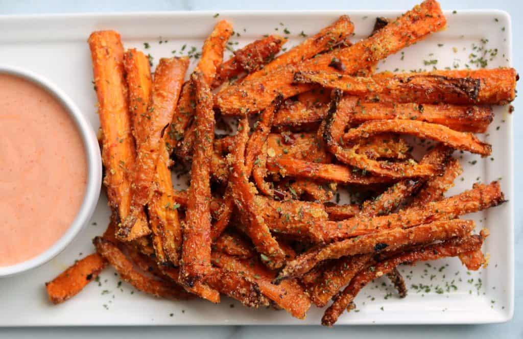 air fried carrot fries on a white plate with Greek yogurt sriracha dip