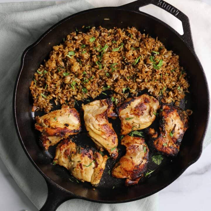 cilantro lime pan fried chicken thighs and rice in cast iron skillet
