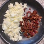 cooked egg whites and bacon in a skillet for breakfast enchiladas