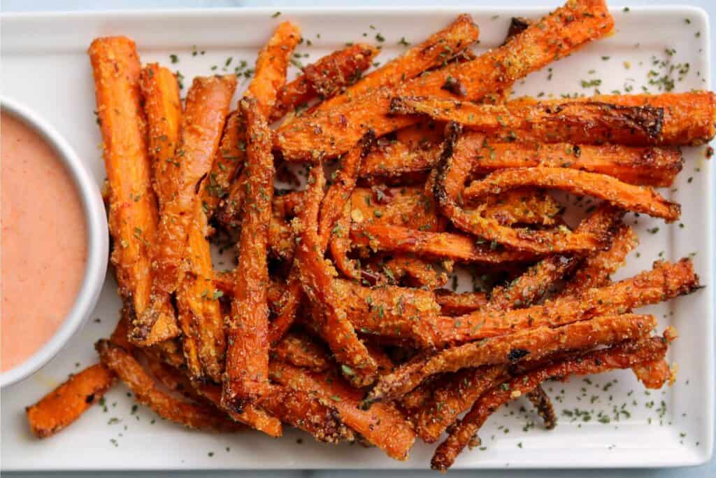 carrot fries on a white plate with dip