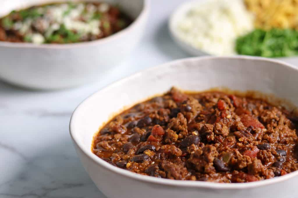 healthy chili with ground beef and black beans in a white bowl