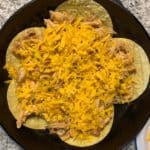 chicken and shredded cheddar on top of the corn tortillas in the cast iron skillet